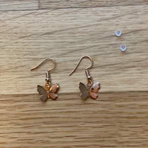 """Säljer dessa sjukt fina örhängen med guldfärgade fjärilar som jag själv gjort! Passar perfekt till alla outfits och ger sån fin detalj! 🤍Obsv ej äkta silver.🤍 Genomskinliga """"ploppar"""" medföljer gratis i priset! Frakten kostar 12 kronor och är en extra kostnad som läggs till i köpet. 🦋🦋"""