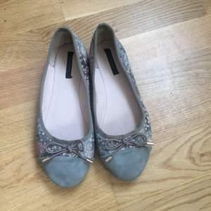 Ballerina skor med fastsydd rosett och mönster. Storlek 36 men är liten i storleken så mer som storlek 35. Är använda men i bra skick. Frakten ingår inte.