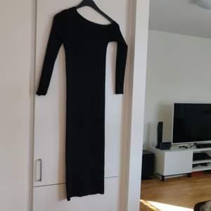 En svart stickad klänning som är nerhasad över ena axeln. Från Zara i storlek S. Fraktkostnaden tillkommer.