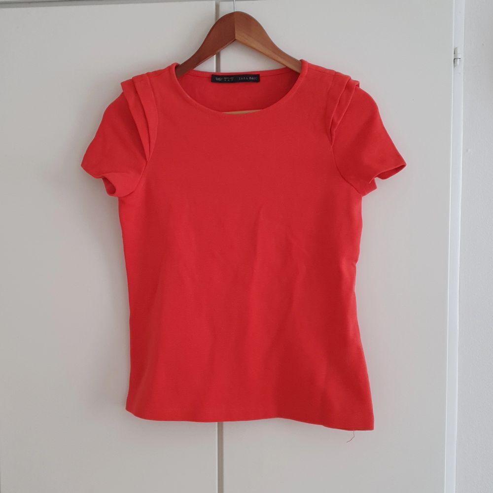 Fin röd orange färg med detaljer på axlarna.. T-shirts.