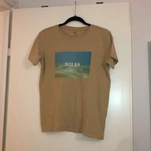 En beige t-shirt med tryck och text från lager 157. Jättefint skick, knappt använd.