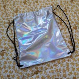 En holografisk väska i gympapåse modell!! Så jäkla snygg men har tyvärr inte använt den. Fint skick, finns någon liten slitning.