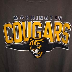 Mörkgrå T-Shirt med stort gult tryck på bröstet. Washington Cougars. Uppvikta ärmar.