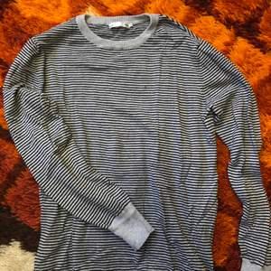Stickad långärmad tröja med grå och svarta ränder. Storlek S från Lager 157. Aldrig använd så är i nyskick! Går att mötas upp i Hagfors eller så skickas den med posten där köparen står för frakten!