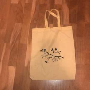 En gul väska som jag köpte på en loppis med ett fågel märke på.
