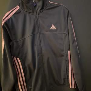 En adidas zipup som är grå och rosa. Står storlek L men jag tycker att den är mer som xs/s i storleken💕