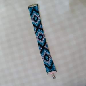 Här är ett handgjort armband jag har gjort som är i typ 20 cm långt. Färger: svart,lila,ljus blå och blå. Kan göras i andra färger kontakta bara mig så kan jag säga i vilka färger jag kan göra i just nu och så kan man säga hur långt man vill ha. Den här