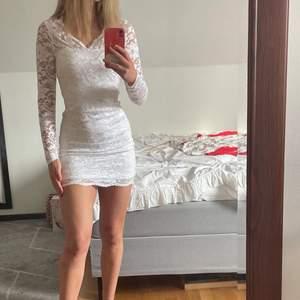 En vit tajt klänning med spets. Långärmad (endast av spets) jag har endast använt den på en skolavslutning för några år sen. 🤍🤍 den är från Nelly.com