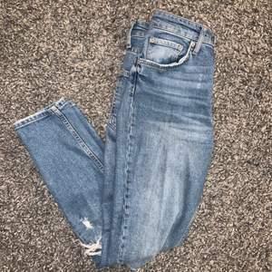 Ett par asfina blåa jeans med hål på knäna ifrån Gina! Det är momjeans modell på dom! Storlek 36! Dom är använda men är i skick som nya! Nypris är 500-600kr. Skriv för funderingar! Köparen står för frakten!🌵