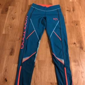 Turkosa/orangea träningstights från Kari Traa. Endast använd ett fåtal gånger, i nyskick! Dragsko i midjan och reflexer på benen, perfekta för löpning. Ficka för nycklar bak. Mer åt det gröna hållet än bilderna visar.