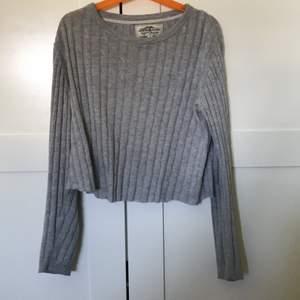 En grå tröja i storleken 134/140