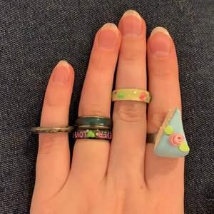 5 i stort sett oanvända ringar. Lillfinger: ring i metall med glasdiamanter inuti = 10kr. Ringfinger: två olika mood rings en basic och en där det står forever love 30kr/styck. Långfinger: självlysande ring med små delfiner 20kr. Pekfinger: justerbar ring med tårta 30kr. Rabatt om man köper flera