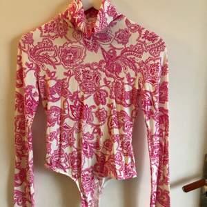 Säljer denna rosa mönstrade bodyn (string) i strl 36. Med polokrage. Köparen står för fraktkostnaden💗