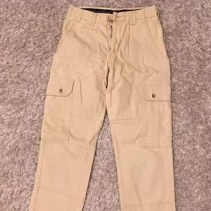 Rejäla workwear byxor i beige kraftig bomull med fickor på sidorna. Storlek 46 men passar bra på storlek 40, för lite oversize stil. Skickar gärna fler bilder och tar mått vid intresse.