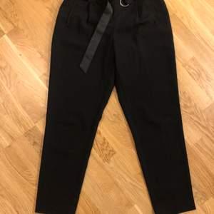 Svarta byxor med hög midja i storlek 40. Helt oanvända och i toppskick. 100% polyester. 100kr + frakt 66kr.