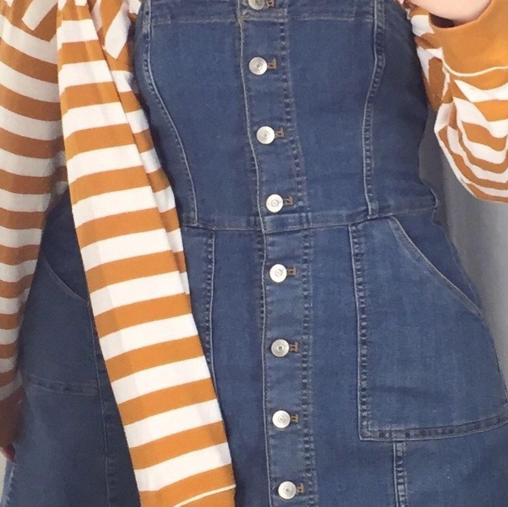 Jeansklänning i storlek 34, justerbara axelremmar!  Jättefin att ha över långarmad tröja! Går över knäna! . Klänningar.