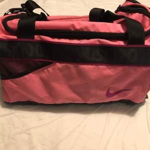 Rosa Nike väska, prefekt för gym eller sport. Köpt för ett par år sen och använd ett fåtal gånger. Finns ett fack på sidan för skor och en liten ficka på insidan för ex. Telefon, har vissa småfläckar.                                               Storlek: 44cm lång och 25cm bred.