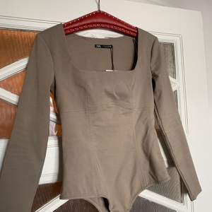 Grå/grön body från Zara. Aldrig använt. Prislapp kvar. Köpt för 259kr. Kan mötas upp i Växjö eller postas. Köparen står för frakt.