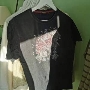 Tshirt i urtvättad svart med tryck fram. Köpt på en vintage butik