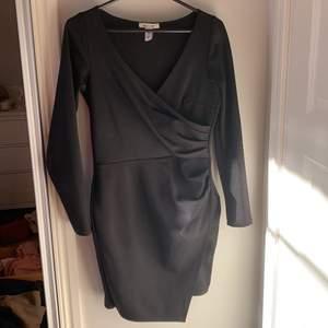 Svart klänning från nlyone i storlek S. Åtsittande, med omlott både vid bröstet och på kjolen.