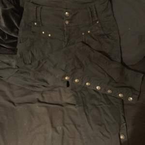 Svarta textil byxor med skit snygga knappar. High waist och skinnyfitt. Har detaljerade knappar längs benen. Så snygga men tyvärr är dom för stora för mig. Topp skick och aldrig använda av mig.                                                     Storlek 38. Köparen står för frakt.