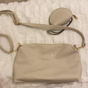 Säljer en beige axelväska med tryck Prada, väskan är inte äkta men är i ett fint skick💖 man får till en liten söt necessär också.