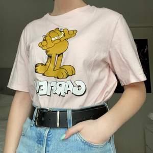 Rosa t-shirt från H&M dividend med katten Gustav motiv. Använd men i bra skick