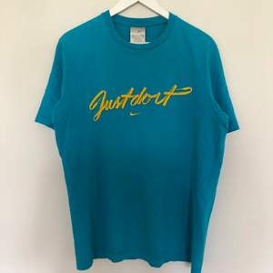 Vintage Nike T-Shirt i storlek Large. Tishan är i fin blå färg med en broderad Mini swoosh på bröstkorgen. Tishan har en silver tag. Vintage skick med lite cracking på texten.