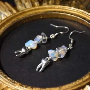 Örhängen med silvriga tandberlocker och äkta opalit.  Krokarna är nickelfria.