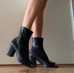 """Ett par fantastiskt sköna """"strump""""-klackskor i svart imitationsskinn från Zara. Blockklack och öppen tå i strl 38. Använda flitigt då de är suuuuuper lätta och sköna att gå i, men inget märke eller fläck på dem. Frakt tillkommer från 66kr (tyngre skor = mer frakt)."""