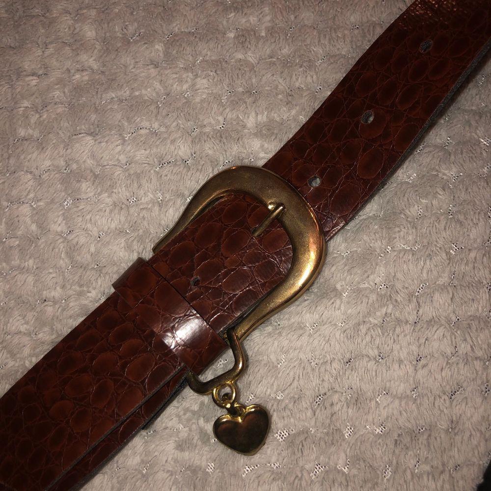 Vintage brunt läderskärp med hjärta✨❤️ hela bältet ee ca 90cm. 70cm till första hålet. Ca 83 cm till sista. Accessoarer.