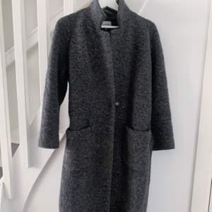 """Grå ullkappa från Ganni i storlek 36/S. Väldigt varm och skön. Använd två vintrar, men fortfarande i finfint skick.   Modellen heter """"Fenn long wrap coat"""". Nypris ca 3500 kr."""