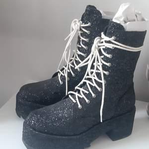 Svarta glittrande Dolls Kill boots,  i storlek 41. Oanvända/nyskick. Påminner lite om rocky horror picture show, visst? Accepterar swisch.
