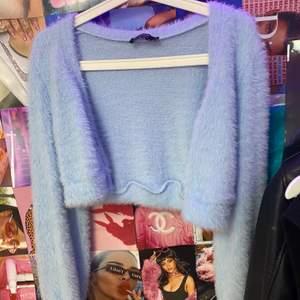 En ljusblå croppd fluffig cardigan med jättefina knappar. Från behrshka och köptes för 259kr och jag säljer för 100kr. Aldrig använd!!!💕💕💕⚡️⚡️