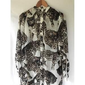 Snygg H&M Conscious«Wild cat» katt lång skjortklänning tunika. Storlek 34, lite stor i storlek. Nyskick. Knappar hela vägen och öppensida. Jättefint silky material. Längd: 112cm . Material: recycled polyester