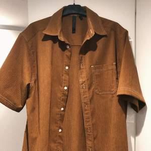 Brun kort armad skjorta i manchester liknade tyg, den är i storlek s men är köpt på herr så den är väldigt oversized. Köpt från asos.