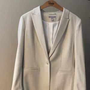Beige kavaj/kostym i strl. 40. Jag köpte plagget hösten 2020 och har inte använt det pga. att den är för stor för mig.