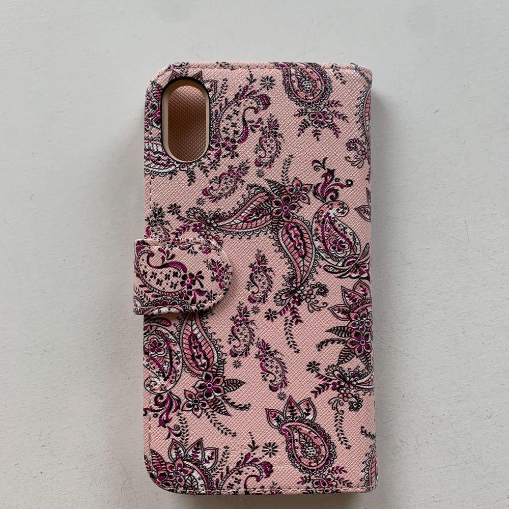Rosa magnetiskt plånboksskal till mobilen med mönster på. Finns plats för tre kort + ett stort fack under. Kommer ifrån holdit och passar iPhone XR. Fint skick, nästan aldrig använt. Skalet kostar 100 kr, frakt ingår ej. Swipe för fler bilder.. Övrigt.