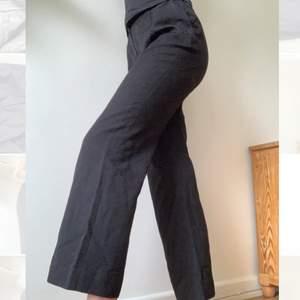 Svarta croppade kostymbyxor från Versace, köpt second hand i Paris så ingen aning om de kan vara äkta eller fejk. Oavsett i väldigt fin kvalité, tunn ull med ett vävt versace-mönster som syns i solljus. Har sytt in dem i midjan så de passar storlek 34 / XS / W25. Ankellånga lite utsvängda ben. (Det som ser ut som ett märke där bak på sista bilden är bara damm) Skickar gärna fler bilder i pm! Hämtas i Malmö eller Lund eller skickas mot att köparen betalar frakt