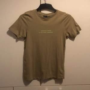 En jätte snygg militärgrön T-shirt med ljusgrön text i fram. Bra skick, andvänd få gånger. Från Ginatricot