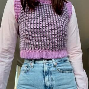 Virkad väst i färgerna grå och rosa. Passar perfekt både över en skjorta men även bara med sig själv.!!!