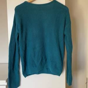 Stickad tröja från NAKD i en superfin grön/blå färg. Har en öppning i ryggen som är format som ett V. Det går även att vända på tröjan om man vill ha en V ringning framtill. Storlek Xs 💕