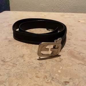 Säljer detta vintage gucci bälte, använd det fåtal gånger. Det är ett svart läder bälte med gucci mönster eunt bältet och loggan på mitten är det ett silver färgat gucci logga