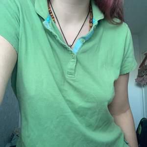 En grön t-shirt med krage och knappar och blå detaljer, aldrig använd!