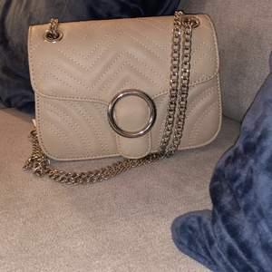 Fin axelremsväska i nyskick i färgen beige, den är aldrig använd
