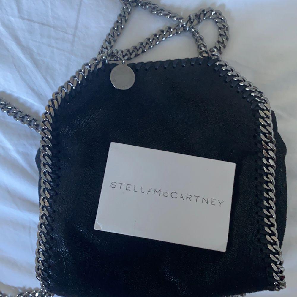 Snygg Stella McCartney väska som är i modellen Tiny. Den är helt ny, plasten på kedjorna är borta men den är i nyskick. Kvittot har jag råkat slarva bort med koden inuti väskan bevisar att den är äkta. Dustbag och kortet medföljer. OBS! Kommer inte gå ner mer i pris!. Väskor.
