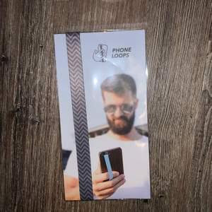 """""""Phone Loop"""" hållare till mobilen. Man sätter fast den i sitt telefonskal, så att man inte tappar sin mobil. Oanvänd. Nypris ca 80kr (+ frakt/tull då den kommer från USA), säljer för 50kr inkl frakt✨"""