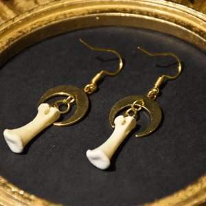 Örhängen med guldiga halvmånar och små ben. Nickelfria krokar.