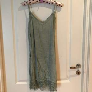 Green silk top/tunic/dress looks and feels like silk, decorated with very beautiful lace at the top and bottom. 61% rayon, 39% viscosa. Made in Italy. Köparen står för frakten.