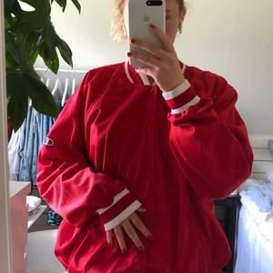 Röd collage-jacka från Champion i ett tunnare material som passar perfekt för sommaren i strl L. Sitter snyggt oversize på mig som vanligtvis har strl M!❤️